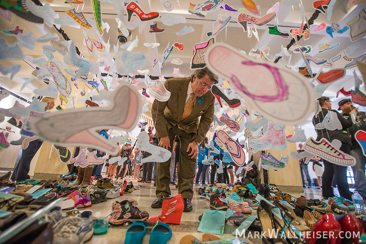 Sen. Gary Farmer Jr., (D- Ft. Lauderdale) looks at a display of 1,000 shoes of victims of sexual violence on display at the Florida Capitol in Tallahassee, Florida for Sexual Assault Awareness Month.  The display is hosted by Lauren's Kids and the Florida Council Against Sexual Violence.