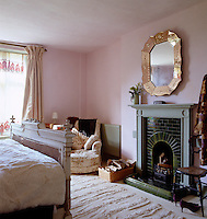 A feminine bedroom has been painted in pale pink with an original glazed brick fireplace