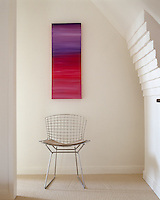 An abstract painting hangs above a classic wire-mesh Bertoia chair next to a curved brick chimney breast in a corridor of a converted country schoolhouse