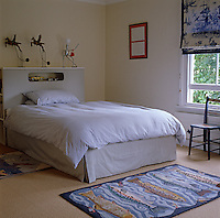 A boy's bedroom is simply furnished with a storage unit doubling as a headboard