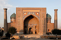 """View from the front of the Sher-Dor Madrasah, 1619-36, Registan, Samarkand, Uzbekistan, pictured on July 15, 2010 at sunset which lights up the elaborately tiled facade and domes. The Sher-Dor Madrasah, commissioned by Yalangtush Bakhodur as part of the Registan ensemble, and designed by Abdujabor, takes its name, """"Having Tigers"""", from the double mosaic (restored in the 20th century) on the tympans of the portal arch showing suns and tigers attacking deer. Samarkand, a city on the Silk Road, founded as Afrosiab in the 7th century BC, is a meeting point for the world's cultures. Its most important development was in the Timurid period, 14th to 15th centuries. Picture by Manuel Cohen."""