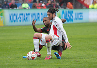 Toronto, Ontario - May 3, 2014: New England Revolution midfielder/forward Lee Nguyen #24 and Toronto FC forward Jermain Defoe #18 in action during a game between the New England Revolution and Toronto FC at BMO Field.<br /> The New England Revolution won 2-1.