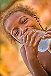 Throughout West Africa, hawkers sell plastic bags filled with ice water for 25 cfa (about five cents!).  Here, in Ouagadougou, Burkina Faso, a young Fulani girl  drinks from a plastic bag filled with the refrigerated water.