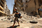 Fouad, a 11-year-old Syrian boy, walks on his way to school in a rebel-controlled area of Aleppo, on August 8, 2015. Fouad works everyday following the school time to provide for his small family, as his father suffers from disease. Children in the country were now contributing to the family income in more than three quarters of Syrian households, according the report released by UNICEF, estimates that one in ten Syrian refugee children in the region is engaged in child labour. Photo by Ameer al-Halbi