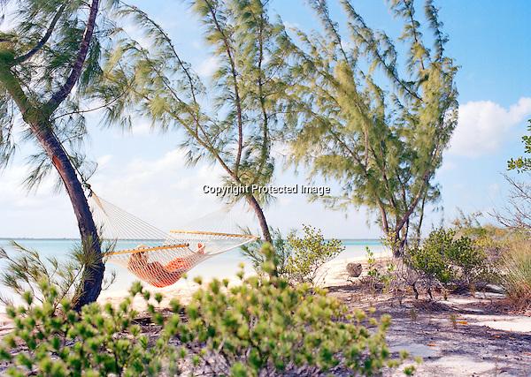 A guest relaxes in a hammock on Tiamo Beach as a catamaran sails by. South Andros Island, Bahamas