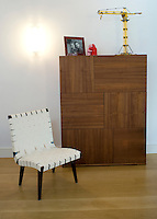 In the living room an unusual chair constructed with white leather webbing has been arranged next to a cupboard with an elegantly simple marquetry front