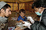 """Following an October 8, 2005, earthquake in northern Pakistan, members of Action by Churches Together in Pakistan, including Church World Service and the Church of Pakistan, responded quickly to the needs of thousands of affected families. Here a physician from Peshawar, Hizkial Barkat (right), a member of a CWS-supported delegation from the Peshawar diocese of the Church of Pakistan, attends to injured patients at a CWS-sponsored """"tent city"""" near Balakot."""