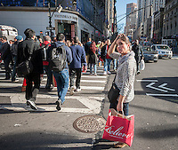 Shoppers laden with their purchases cross Herald Square in New York on the day after Thanksgiving, Black Friday, November 27, 2015. The National Retail Federation estimates that 135.8 million American will shop in person and online during the four day Thanksgiving weekend.  (© Richard B. Levine)