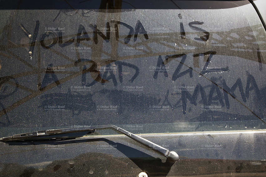 """Philippines. Province Eastern Samar. Hernani. A man wrote words on dirty rear window of a car: """"Yollanda is a bad ass, Mama"""". 95 % of the town was destroyed by typhoon Haiyan's winds and storm surge. Typhoon Haiyan, known as Typhoon Yolanda in the Philippines, was an exceptionally powerful tropical cyclone that devastated the Philippines. Haiyan is also the strongest storm recorded at landfall in terms of wind speed. Typhoon Haiyan's casualties and destructions occured during a powerful storm surge, an offshore rise of water associated with a low pressure weather system. Storm surges are caused primarily by high winds pushing on the ocean's surface. The wind causes the water to pile up higher than the ordinary sea level. 25.11.13 © 2013 Didier Ruef"""