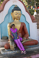 Kathmandu, Nepal.  Young Nepali Woman Reclines in the Lap of One of Many Buddhas Lining the Stairs Leading to the Swayambhunath Temple, as a Friend Takes her Picture.  This Buddha shows the all-seeing, all-knowing third eye in the middle of the forehead.