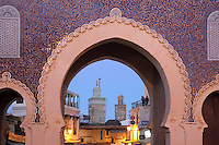 Bab Boujloud or Blue Gate, a huge gateway to the medina of Fes, Fes-Boulemane, Northern Morocco. The gate was built by the French in 1913 next to the 12th century original in Mauresque Andalusian style, with horseshoe arches decorated with Fassi blue tiles on the outside and green tiles on the inside, in patterns of stars and swirls. Through the arch are the minarets of the 20th-century Sidi Lazzaz mosque (right) and the restored 14th-century Bouinania Madrasa (left). The medina of Fes was listed as a UNESCO World Heritage Site in 1981. Picture by Manuel Cohen