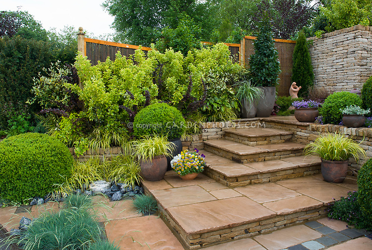 Landscaping in backyard with tiered stone patio with privacy fence
