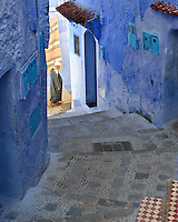 A man in a traditional djellaba walks through the mesmerizing blue streets of Chefchaouen (at the foot of the Rif mountains of Morocco)