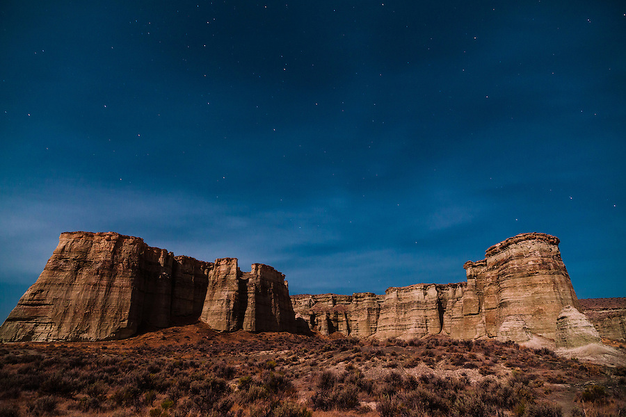 The sandstone cliffs of the Pillars of Rome in Southeast Oregon stand among a sagebrush-filled landscape on a quiet night.