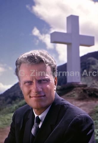 Reverend Billy Graham beneath giant cross at Kolekole Pass, Hawaii, 1963. Photo by John G. Zimmerman.