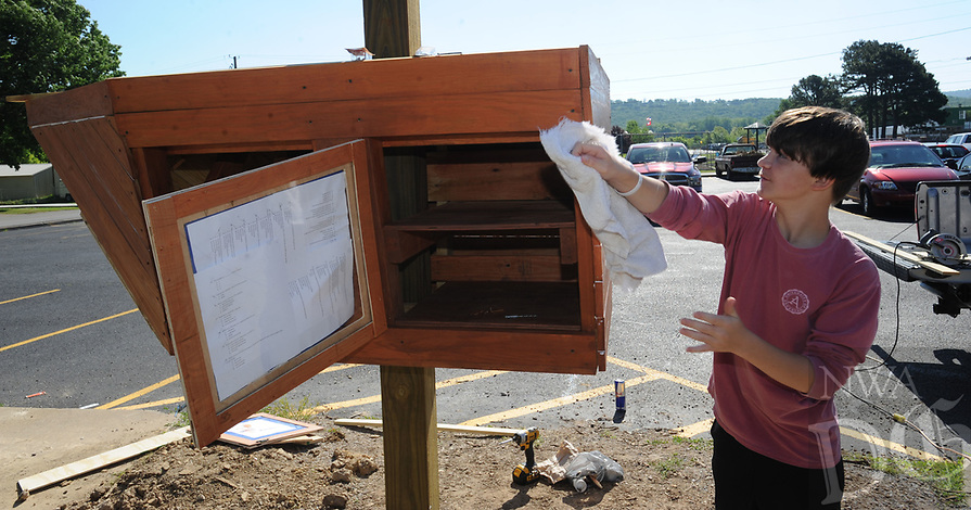 NWA Democrat-Gazette/ANDY SHUPE<br /> David Sanford (right), 13, an eighth-grader at Greenland Middle School, works with friend Dylan Wright Tuesday, May 16, 2017, to install a Little Free Library by Sanford to resemble a Pirate ship outside the school, the mascot of which is the Pirate. Sanford is completing a year-long project for his Environmental and Spatial Technologies class at the school. The ship will house and protect books that are free to others on a take-one, leave-one basis.