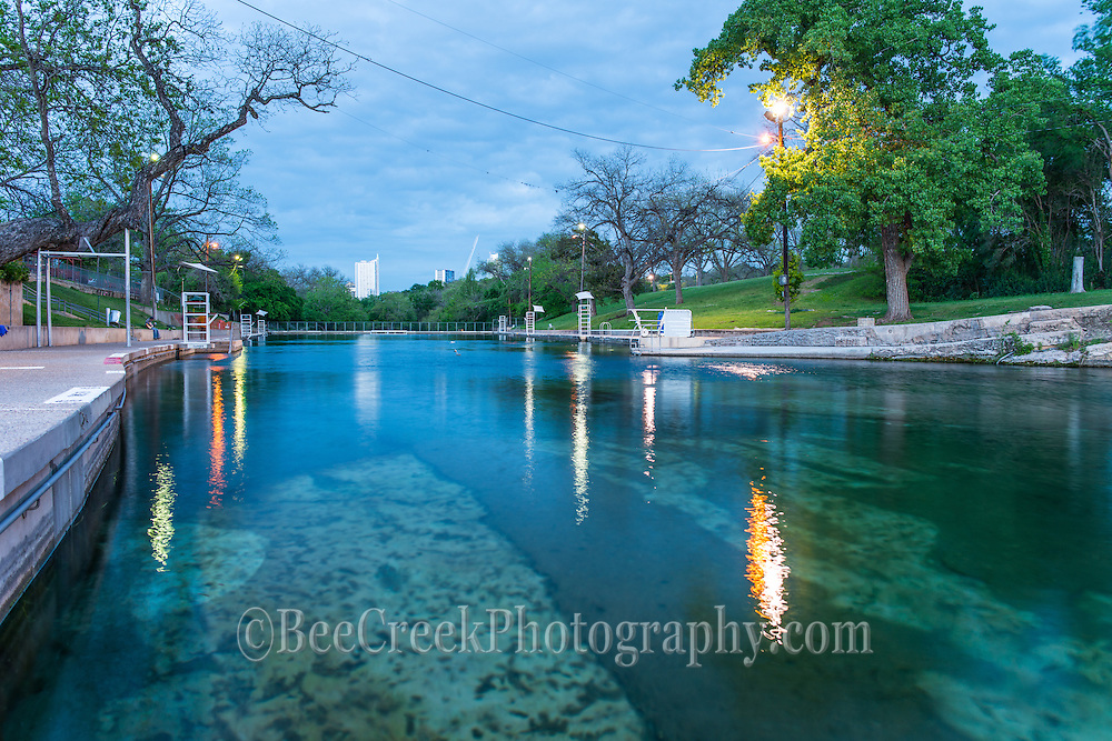 Barton Springs Pool at night. Many people do not realize that the pool is open in the evening for a dip in the cool waters or to do some laps. In the distance you can see the city of Austin.
