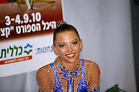 """Melitina Staniouta of Belarus smiles to camera at """"kiss & cry"""" during event finals at 2010 Holon Grand Prix at Holon, Israel on September 4, 2010.  (Photo by Tom Theobald)."""