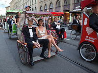 Germany. Bavaria state. Munich. A happy newly wed couple rides a tricycle on the Maximilianstrasse. A procession of cycle rickshaws carry the wedding guests. The cycle rickshaw is a small-scale local means of transport; it is also known by a variety of other names such as bike taxi, velotaxi, pedicab, bikecab, cyclo, beca, becak, trisikad, or trishaw. Cycle rickshaws are human-powered by pedaling. They are a type of tricycle designed to carry passengers on a for hire basis. 30.08.14 © 2014 Didier Ruef
