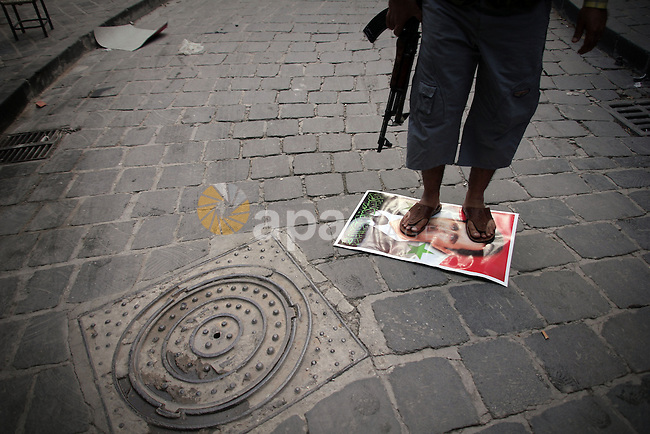 A Syrian rebel fighter stands on a picture of Syrian President Bashar al-Assad, in the Old Town of Aleppo, September 11, 2012 during clashes with Syrian government forces to retake control of the large Hanano army base in Aleppo. Photo by Ahmed Deeb