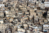 Jordan. Amman. Downtown. Town center. A muslim man drives his car on a narrow road while a red car is parked on the street. Traditionnal buildings and constructions where are set on most of the roofs watertanks and parabolic aerials to get better reception on television programms. © 2002 Didier Ruef