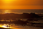 Silhouetted runners along ocean beach at sunset Northern California Carmel California USA.