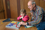 Berkeley CA  Grandpa and granddaughter, four-years-old playing strategy game, Blokus, together  MR