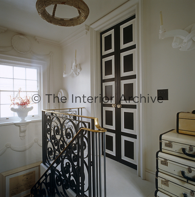 The staircase ends at an elegant double door with square panels at the top of the house