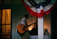 A woman with guitar at the family looks through memorabilia on the front porch of the family homestead before an evening concert. Up to 1000 relatives gather at the homestead of the Tatum family for a reunion and three day celebration.