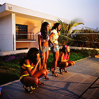 Four scantily dressed women watch on during the production of a Kuduru/Kuduro music video being shot at a private villa on the outskirts of Luanda that is worth in the region of USD 6,000,000....
