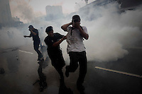 """A supporter of the """"Bersih"""" electoral reform coalition is detained in a cloud of tear gas during clashes in downtown Kuala Lumpur July 9, 2011. Malaysian police fired tear gas and detained more than 500 people in the capital on Saturday in a bid to prevent thousands of anti-government protesters from putting on a massive show of strength against Prime Minister Najib Razak.  REUTERS/Damir Sagolj (MALAYSIA)"""