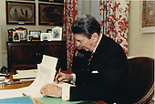 United States President Ronald Reagan signs H.J. Resolution 523 in his study in the Residence of the White House in Washington, D.C. on Friday, April 1, 1988.  The resolution provides for a transfer of 47.9 millionU.S.  dollars from the Department of Defense (DoD) to the Agency for International Development (AID), plus an un-specified amount for transportation costs associated with providing assistance, to support peace and democracy in Central America.Mandatory Credit: Bill Fitz-Patrick - White House via CNP