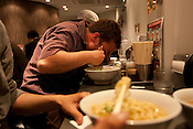 Nate Shockey (pink shirt) eats his noodles in 'Tetsu', a Hakata city-style ramen restaurant in Keonji district, in Tokyo, Japan, Friday 30th April 2010.
