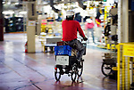A worker makes a delivery by bicycle at Nissan Motor Co.s assembly plant in Tochigi, Japan on Thursday 12 Nov.  2009.