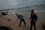 Vietnamese children play during the morning fish market on Mui Ne beach.