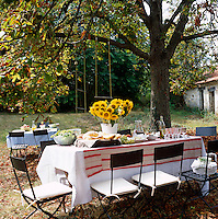 Metal garden chairs with squab cushions and a rustic table draped in elegant linen with a striped cloth under a spreading tree make for an impromptu lunch 'al fresco'