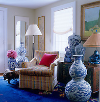 A cheerful striped armchair in the living room is surrounded by a collection of blue and white Chinese ceramics