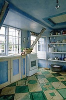 The bright and sunny kitchen is situated on the top floor of the three-storey house and was hand-painted in green and blue by Gonzalo Gorostiaga