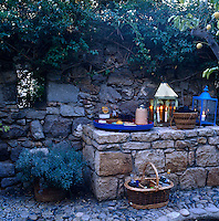 A stone table by the wall offers the perfect setting for setting up a portable bar for an evening aperitive