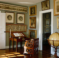 A collection of antique prints and gilt-framed paintings hangs on the walls in this corner of the living room