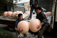 "Workers transport an art installation in Beijing. The sculpture, titled ""Bubbles"" by 33-year-old Chinese artist Shu Yong, is being exhibited at the Wine Factory art space."