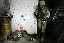 FALLUJAH, IRAQ - November 13: U.S. Army 1st Infantry Division 2nd Battalion-2nd Regiment Sergeant Randy Laird from Lake Charles, Louisiana  walks past the body of a slain Iraqi insurgent November 13, 2004 during a sweep of southern neighborhoods in the Iraqi insurgent stronghold of Fallujah. U.S. and Iraqi forces continue to push deeper into the city in their combined effort to rid Fallujah of insurgents and foreign fighters ahead of the planned January national elections.