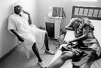 "Cameroon. Douala. ""L'Aquintinie"" hospital. Day service.                                                                                                   Aids infection. Young woman HIV Aids positive with her sister. The woman lying down in bed receives some drugs because of bad side effects of her anti-retroviral  (ARD) treatment. © 2001 Didier Ruef"