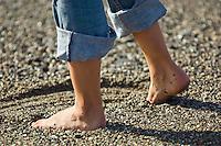 Female's feet in rocky sand