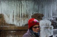 New York, United States. January 23, 2013. .A woman poses for a picture next to a fountain with ice during a cold Temperature under zero in New York City  -- . Photo by Eduardo Munoz Alvarez / VIEWpress.