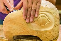Tlingit wood carver, Tommy Joseph carves alder wood at the Sitka National Historic Park in the coastal town of Sitka, Alaska
