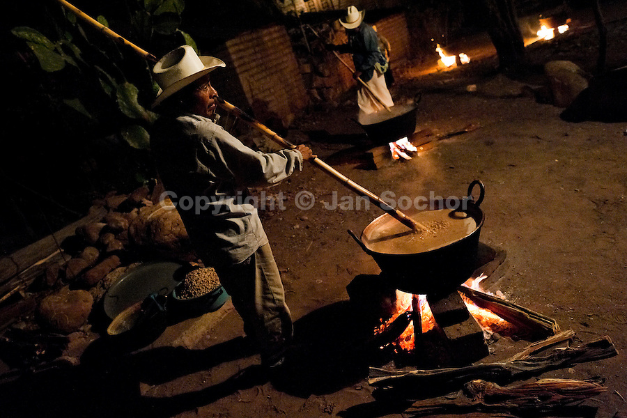 """A Cora Indian man stirs beans in a big pot on the open fire during the sacred ritual ceremony of Semana Santa (Holy Week) in Jesús María, Nayarit, Mexico, 21 April 2011. The annual week-long Easter festivity (called """"La Judea""""), performed in the rugged mountain country of Sierra del Nayar, merges indigenous tradition (agricultural cycle and the regeneration of life worshipping) and animistic beliefs with the Christian dogma. Each year in the spring, the Cora villages are taken over by hundreds of wildly running men. Painted all over their semi-naked bodies, fighting ritual battles with wooden swords and dancing crazily, they perform demons (the evil) that metaphorically chase Jesus Christ, kill him, but finally fail due to his resurrection. La Judea, the Holy Week sacred spectacle, represents the most truthful expression of the Coras' culture, religiosity and identity."""