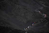 Hikers ascend a trail on cooled lava on Volcan Pacaya in Guatemala.