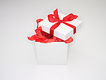 Open gift box with red tissue paper