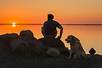 Man and man's best friend watching the sunset in Sequim WA, at Cline Spit lagoon.